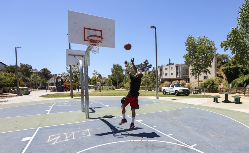 A man plays basketball at the Wightman Street Neighborhood Park in City Heights Tuesday