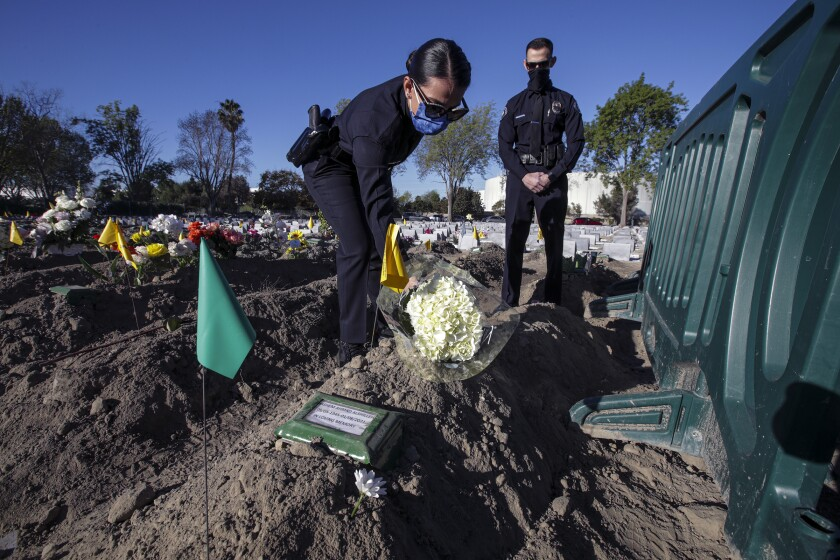 Two people place flowers at a gravesite