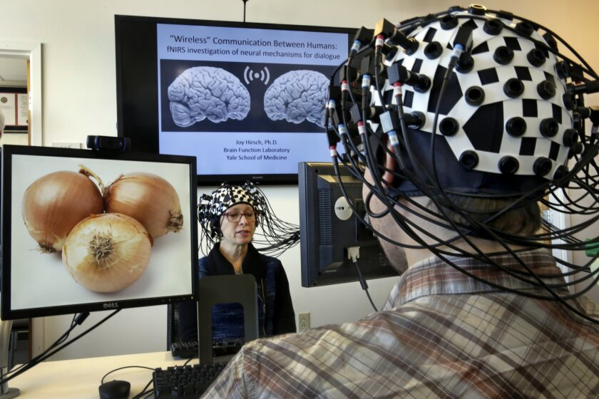 Shaw Bronner, left, and Shaul Yahil, two researchers at the Yale Brain Function Lab, describe images on their computer screens to each other while their brain activity is mapped during a demonstration of the technology in New Haven, Conn. on Friday, March 13, 2015. At one end of each of the 64 fibe