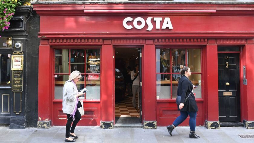 Pedestrians walk past a Costa Coffee in London on Friday.