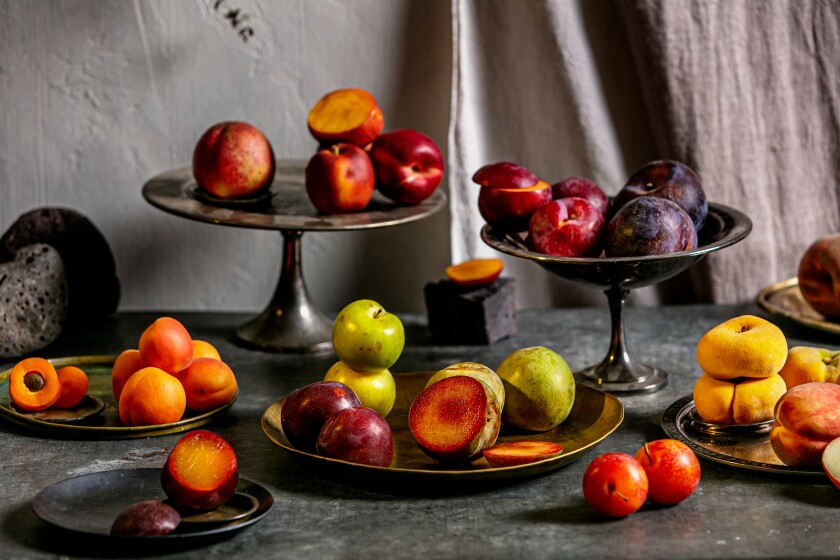 A selection of stone fruits (plums, pluots, nectarines, apricots and peaches), some cut, others whole, in bowls