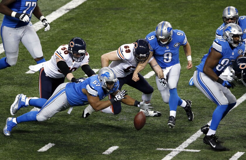Detroit guard Rob Sims (67), Chicago defensive end Jared Allen (69) and Lions quarterback Matthew Stafford (9) try to recover a fumble during the teams' game on Thanksgiving Day.