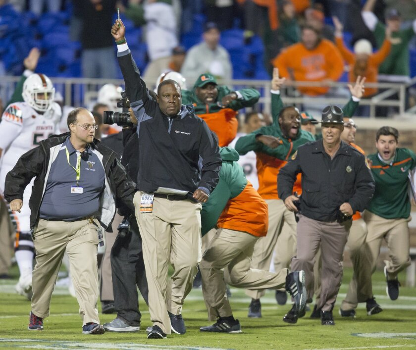 FILE - In this Saturday, Oct. 31, 2015, file photo, Miami's interim head coach Larry Scott raises his hand after defensive back Corn Elder returned a kickoff, which featured multiple laterals, and scored to defeat Duke 30-27 in an NCAA college football game in Durham, N.C. The once-in-a-lifetime pl