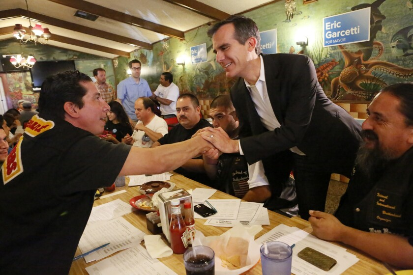Eric Garcetti shakes hands with Donald Galaz as he meets with dock workers and other backers at a Wilmington restaurant in May while campaigning for mayor of Los Angeles.