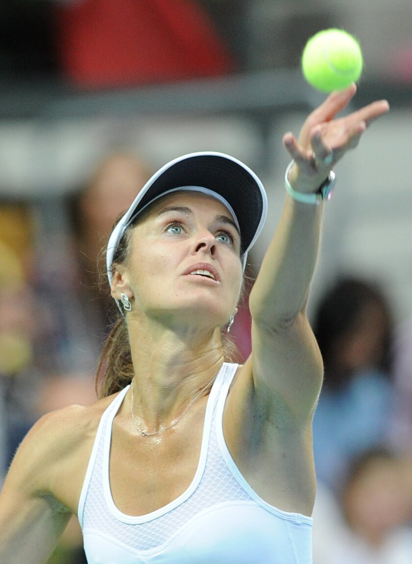 Switzerland's Martina Hingis serves  a  ball  to Poland's Agnieszka Radwanska during their Fed Cup World Group Playoff tennis match between Poland and Switzerland, in Zielona Gora, Poland, Saturday, April 18, 2015.  Five-time Grand Slam champion Martina Hingis  played  her first competitive singles