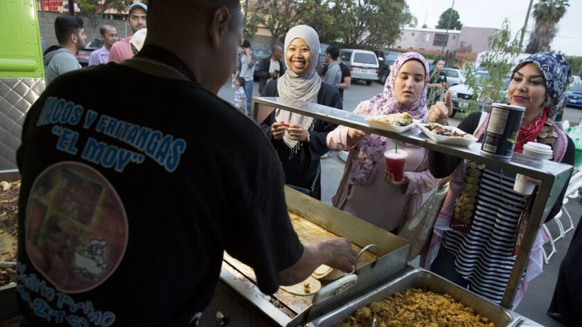 People line up at a taco truck in the parking lot of the Islamic Center of Santa Ana for a 'Taco Tru