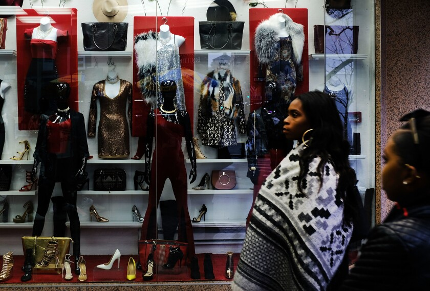 People walk past a store window in downtown Brooklyn on February 23, 2018 in New York City. Americans are more glum now than they were during the Great Recession, according to the Gallup-Sharecare Well-Being Index.