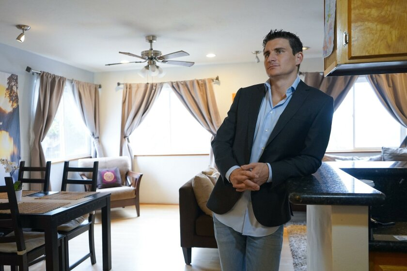 Ryan Scott, a prolific short-term rental host, stands in the living room of a one-bedroom Mission Beach apartment he owns and rents out on multiple vacation rental platforms, including Airbnb.