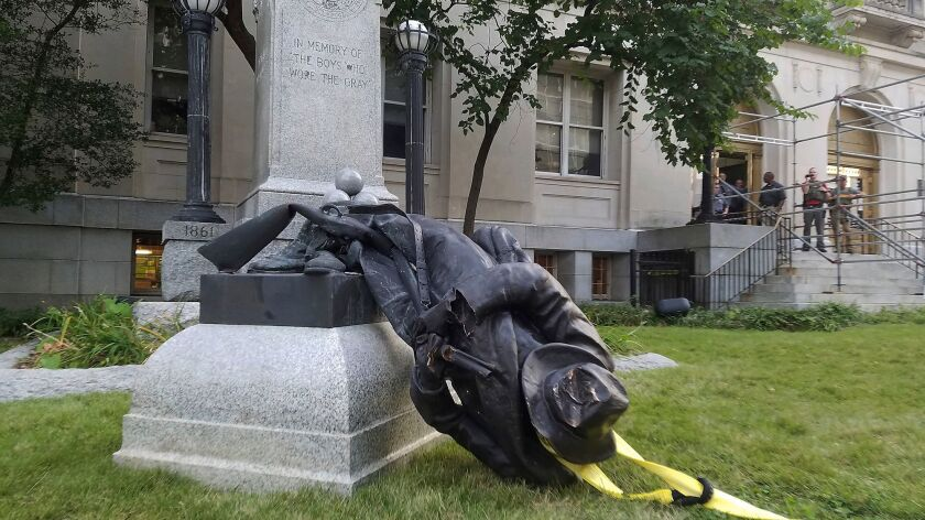 A toppled Confederate statue lies on the ground on Aug. 14, 2017, in Durham, N.C.