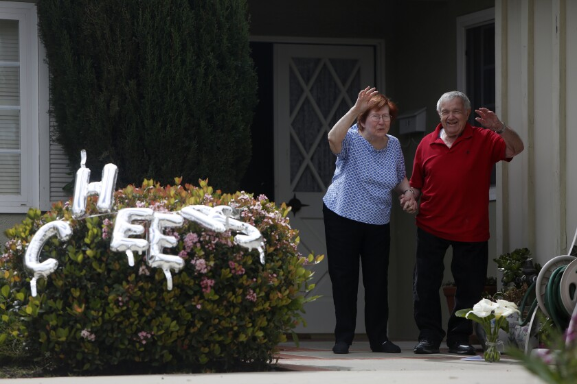 Libby and Harry Polakow greet neighbors who gathered Wednesday in Granada Hills to celebrate their 70th wedding anniversary.