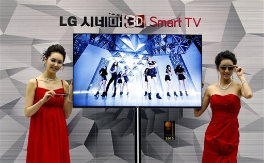 """FILE - In this Thursday, Jan. 19, 2012, file photo, South Korean models pose with a CINEMA 3D Smart TV during a press conference to introduce the LG Electronics' television and the company's marketing strategy for 2012 in Seoul, South Korea. Hewlett-Packard said Monday, Feb. 25, 2013, it is selling its webOS operating system technology to South Korea's LG Electronics Inc. for an undisclosed sum. Hewlett Packard Co. and LG said on Monday that LG will use webOS to support its """"smart TV"""" technology. (AP Photo/Ahn Young-joon)"""