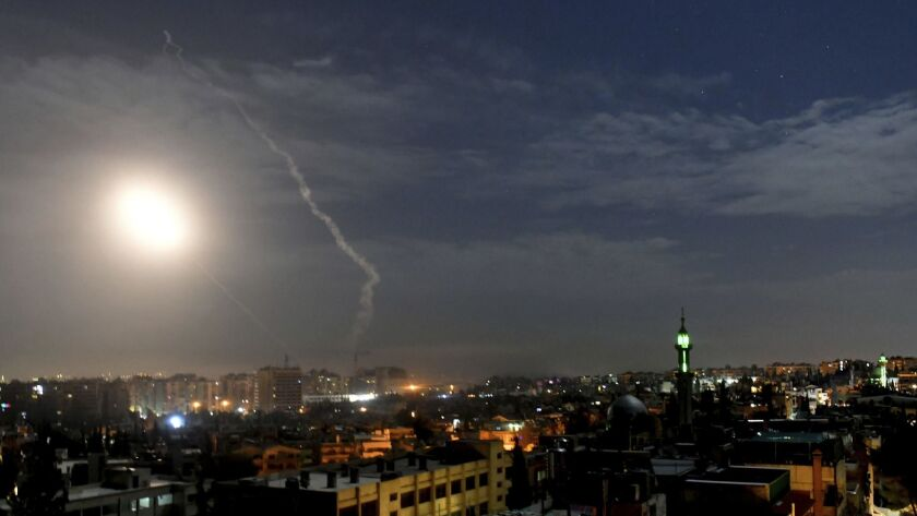 This photo released by the Syrian official news agency SANA, shows missiles flying into the sky near