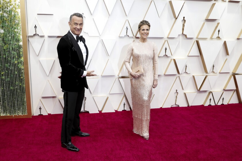 Tom Hanks gestures toward his wife, actress Rita Wilson, on the red carpet at the 92nd Academy Awards.