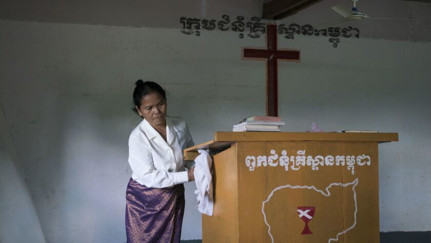 Morm Phin, 75, prepares for Sunday service. Morm was working as a supervisor in a garment factory during the Khmer Rouge's regime and she is now a pastor in a small church outside Pailin town.