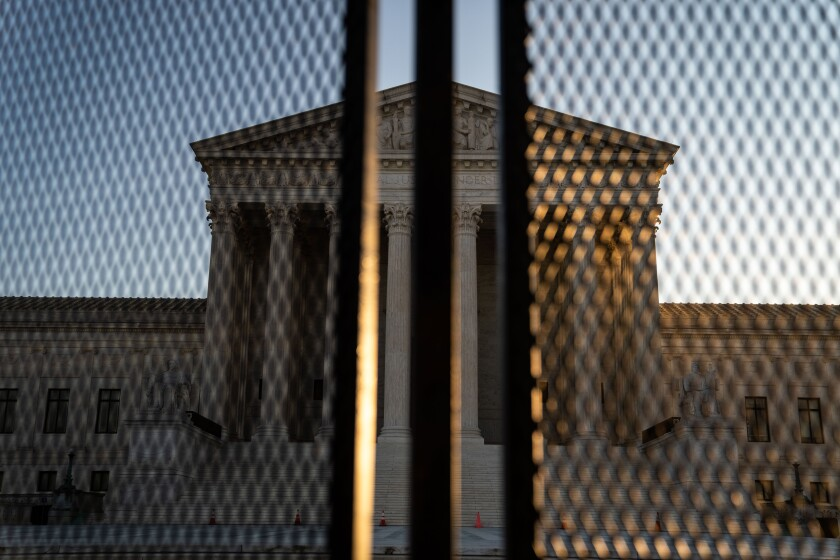The Supreme Court's Neoclassical pediment is seen through security fencing