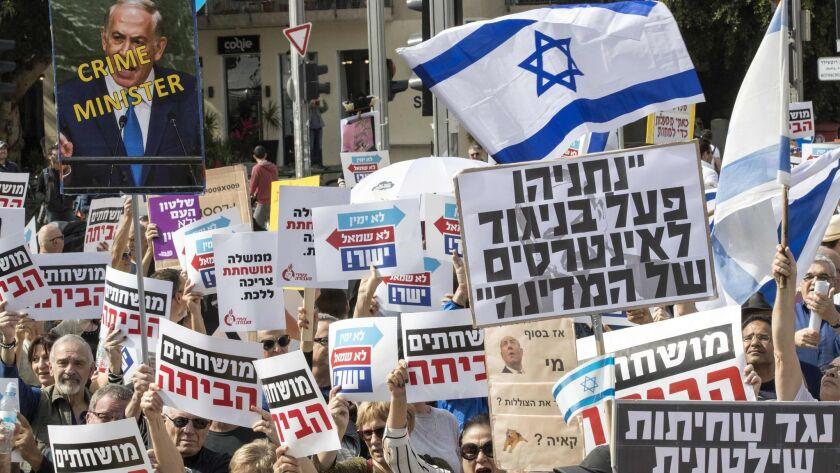 Israeli protesters wave signs critical of Prime Minister Benjamin Netanyahu in Tel Aviv on Feb. 16, 2018.