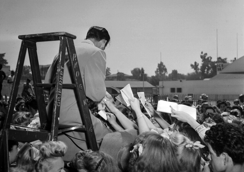 Aug. 11, 1943: Frank Sinatra retreats to a ladder for refuge as autograph hounds besiege him following his arrival by train in Pasadena.