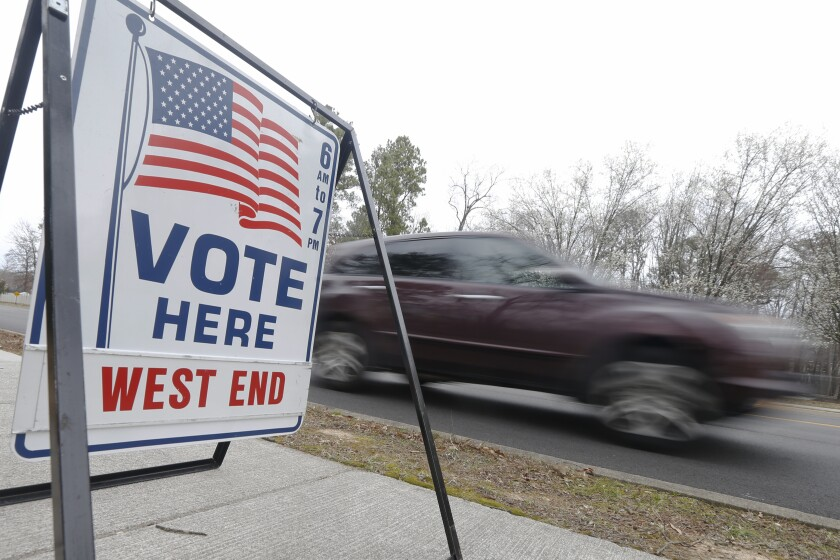A car passes a polling precinct during the Democratic Presidential primary voting Tuesday, March 3, 2020, in Richmond, Va. (AP Photo/Steve Helber)