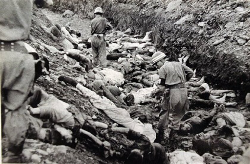 "FILE - In this July 1950 U.S. Army file photograph once classified ""top secret,"" South Korean soldiers walk among some of the thousands of South Korean political prisoners shot at Taejon, South Korea, early in the Korean War. Shutting down its inquiry into South Korea's hidden history, a government"