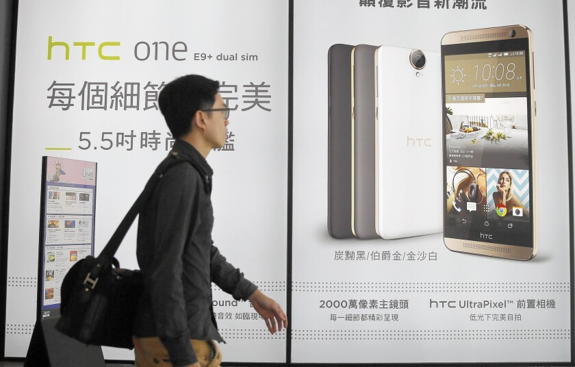 HTC's One series high-end smartphones sold well initially in 2013, but consumer interest dropped off after a lack of new must-have features. Above, a man walks past an HTC ad in Taipei, Taiwan.