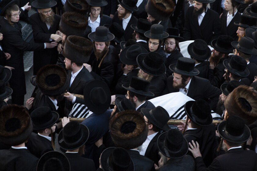 Ultra-Orthodox men carry the bodies of Moshe Englard, 14, and his brother, Joshua, 12, who died during Lag BaOmer celebrations at Mt. Meron in northern Israel, in Jerusalem on Friday, April 30, 2021. A stampede at the religious festival attended by tens of thousands of ultra-Orthodox Jews in northern Israel killed dozens of people and injured about 150 early Friday, medical officials said. It was one of the country's deadliest civilian disasters. (AP Photo/Ariel Schalit)