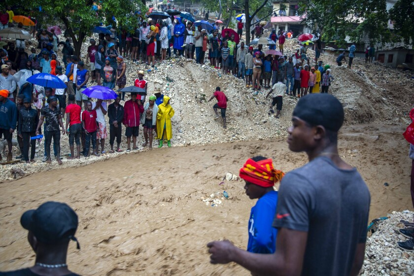 Locals stand on the banks of the Tet Dlo River during the passing of Tropical Storm Laura in Port-au-Prince, Haiti.