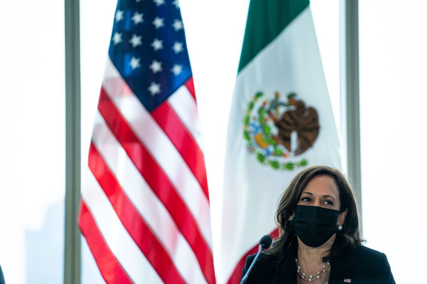 Vice President Kamala Harris wears a mask in front of the U.S. and Mexican flags.