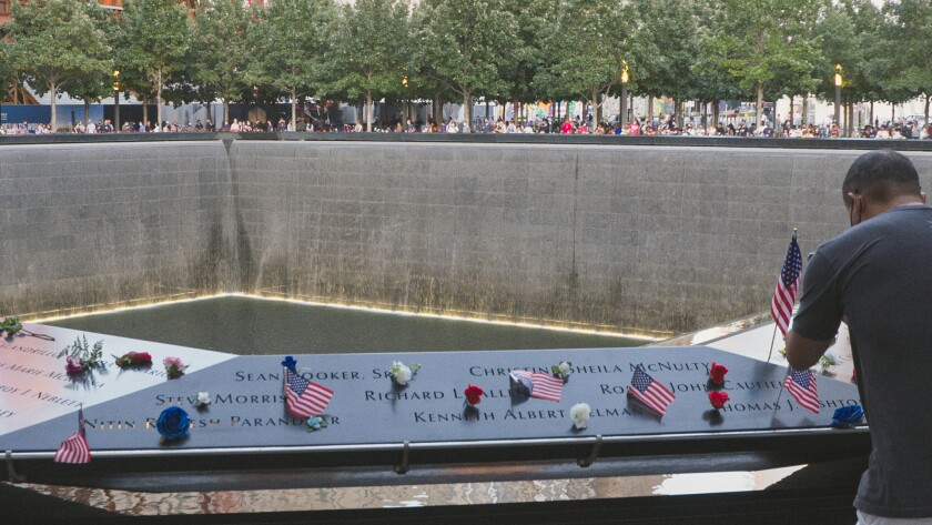 Small American flags and flowers placed on a panel of names