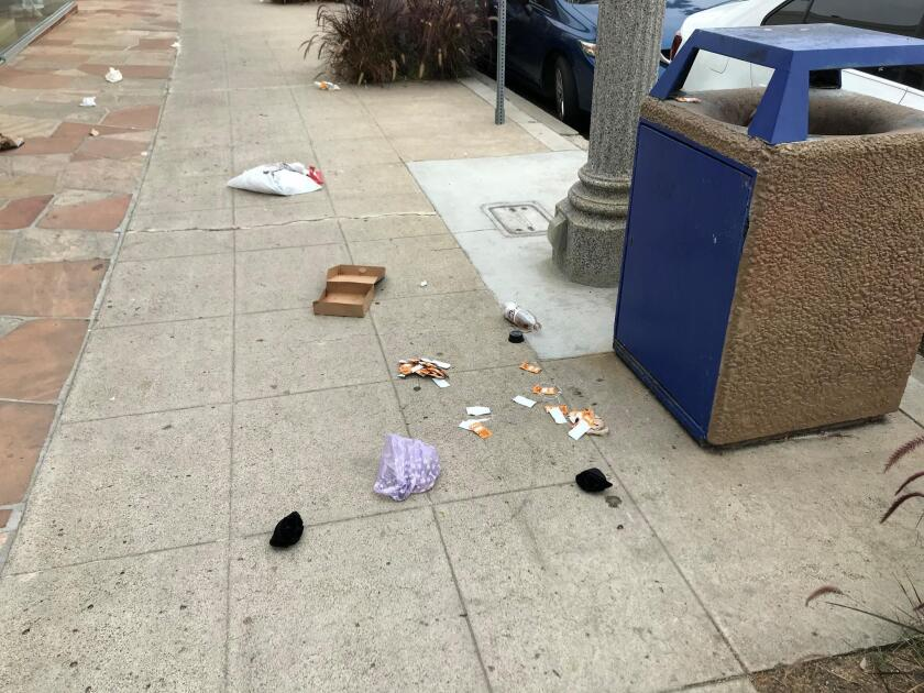 Trash is seen scattered only inches away from a public trash bin on Prospect Street and Roslyn Lane in La Jolla.