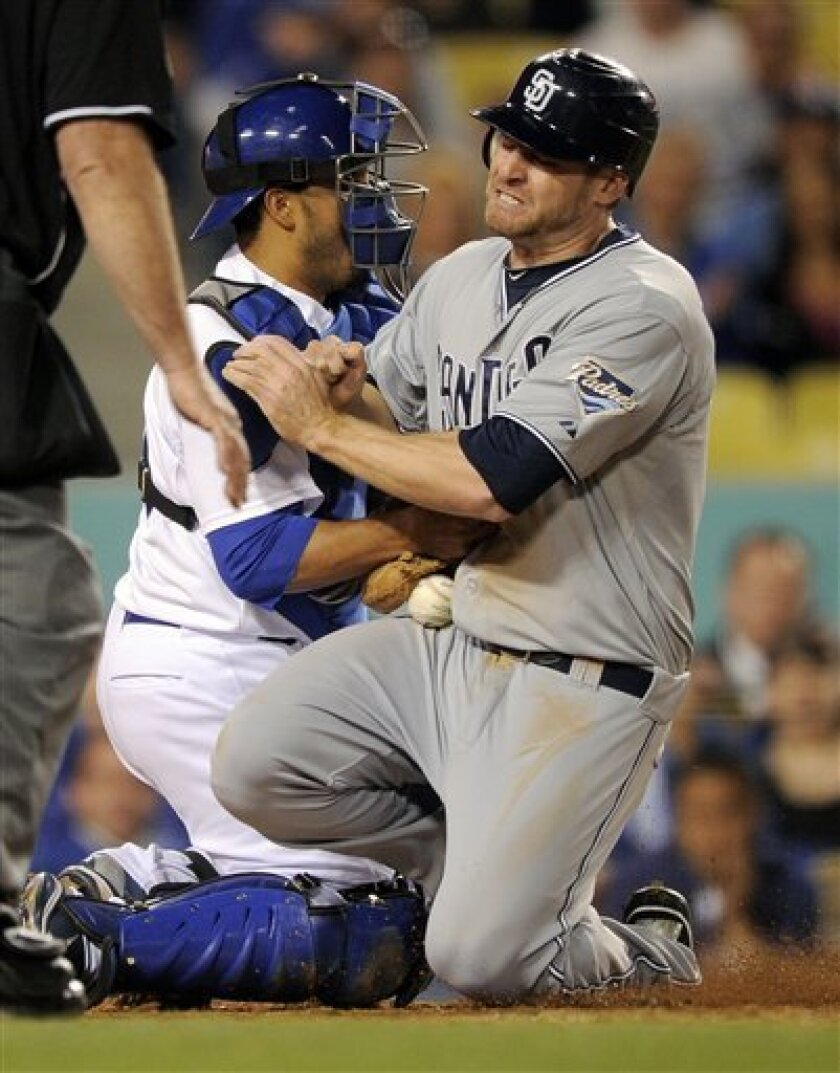San Diego Padres' Chase Headley, right, scores on a single by Cameron Maybin as Los Angeles Dodgers catcher Rod Barajas drops the ball during the eighth inning of their Major League Baseball game, Saturday, April 30, 2011, in Los Angeles. (AP Photo/Mark J. Terrill)