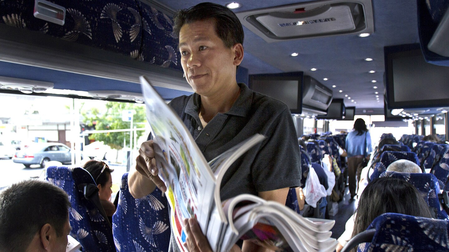 Bus driver Tam Le passes out Vietnamese newspapers to passengers before heading to San Jose. The Xe Do Hoang bus line connects Little Saigon with San Jose, the two largest Vietnamese American communities in the country.