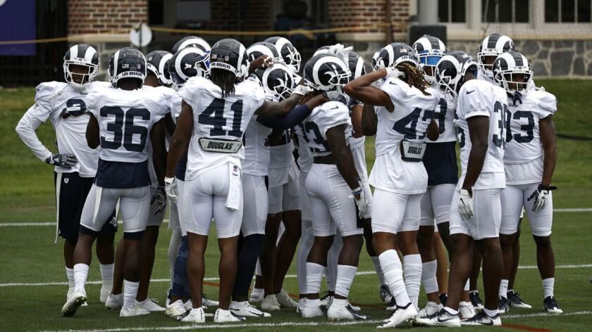 Members of the Los Angeles Rams huddle during a joint NFL football training camp practice at the Bal
