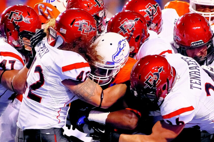 D.J. Harper of Boise State is brought down by a large contingent of San Diego State defenders on Saturday night. The Aztecs' defense played a large role in the team's upset of the Broncos. Otto Kitsinger III • Getty Images Photos