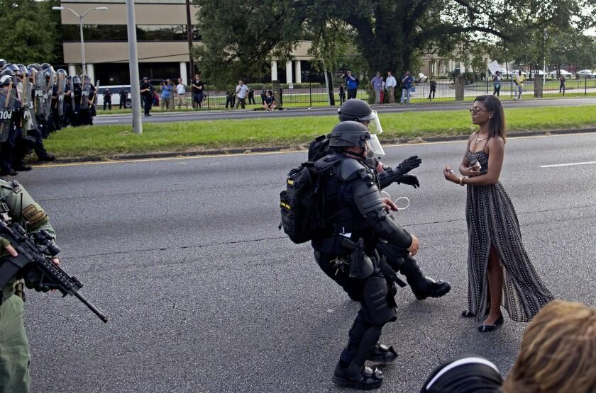Policías armados y con equipo antidisturbios detienen a una manifestante que rehúsa retirarse de una carretera frente a la Estación del Departamento de Policía de Baton Rouge, en Louisiana, el sábado 9 de julio de 2016. (AP Foto/Max Becherer)