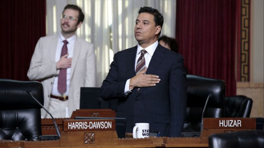 LA City Councilman Jose Huizar says the pledge of allegiance after appearing at his first City Council meeting since his home and offices were raided by the FBI.