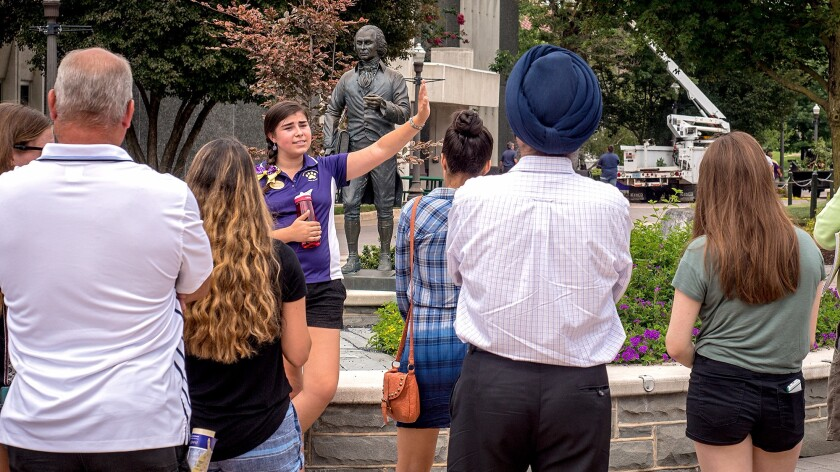 A James Madison University tour guide leads a group of prospective high school students around campus on Aug. 1 in Harrisonburg, Va.