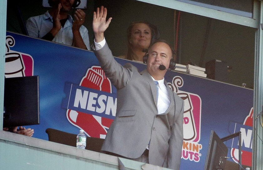 Sports announcer Don Orsillo waves from the broadcast booth following a video tribute during the eighth inning of a baseball game between the Boston Red Sox and the Baltimore Orioles in Boston, Sunday, Sept. 27, 2015. (AP Photo/Michael Dwyer)