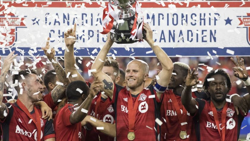 Toronto FC captain Michael Bradley lifts the Voyageurs Cup after Toronto defeated the Vancouver Whit