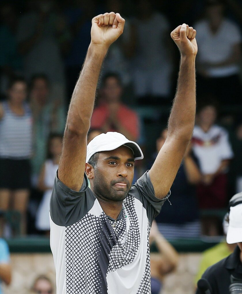 Rajeev Ram celebrates after defeating Ivo Karlovic, of Croatia, in the Tennis Hall of Fame Championship final in Newport, R.I., Sunday, July 19, 2015. (AP Photo/Michael Dwyer)