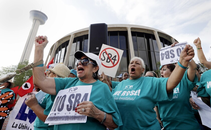 """Lydia Balderas, left, and Merced Leyua join others at a protest against a """"sanctuary cities"""" bill outside federal court in San Antonio in June."""