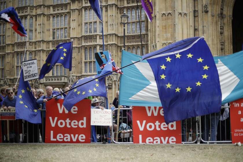 FILE - In this Sept. 3, 2019, file photo, leave and remain supporters try to block each others' banners as they protest opposite Parliament Square in London. Internet companies say they're working to fight misinformation ahead of next month's general election in the United Kingdom, but bogus online claims and misleading political ads remain a threat due to government inaction. (AP Photo/Matt Dunham, File)