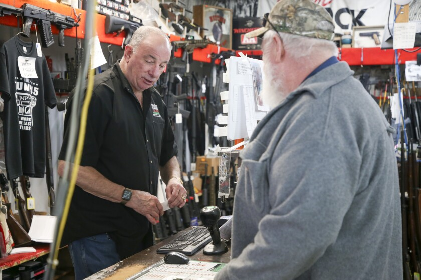 David Stone closes a sale with a customer at Dong's Guns, Ammo and Reloading in Tulsa, Okla.