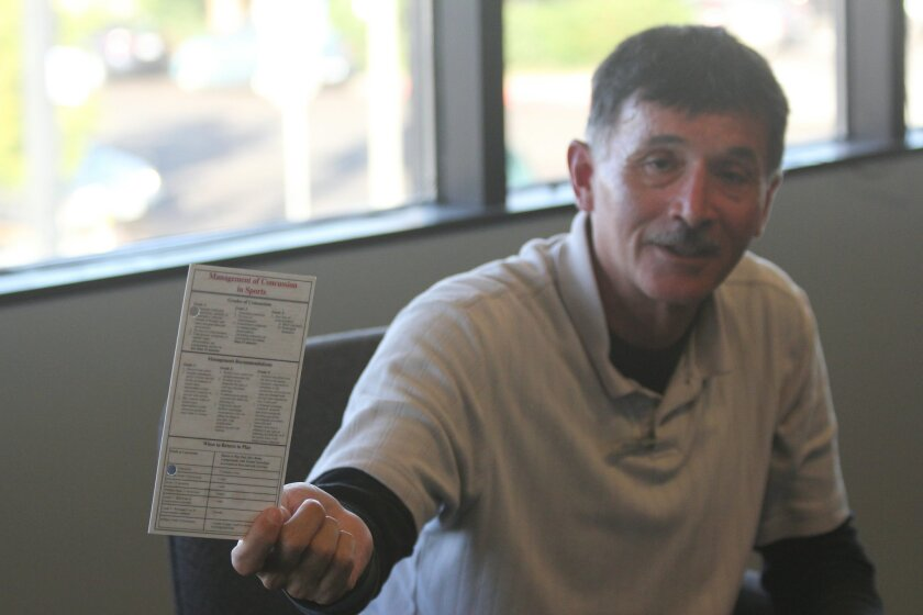 Rey Hernandez, La Jolla High School's former head football coach, holds a card he carried with him during games and practices that lists the signs of a concussion and recommendations for how to respond to head injuries — a tool now widely employed by NFL coaches.