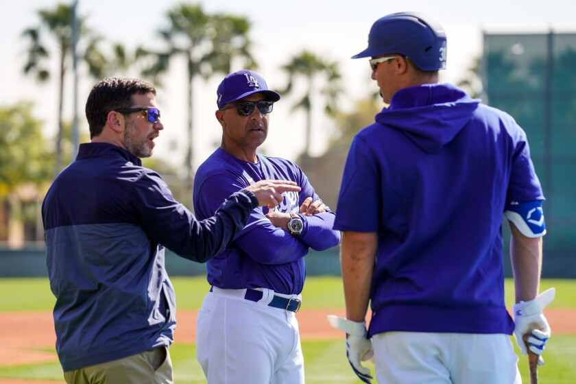Dodgers president of baseball operations Andrew Friedman, left, manager Dave Roberts and Joc Pederson talk during spring training Wednesday at Camelback Ranch.