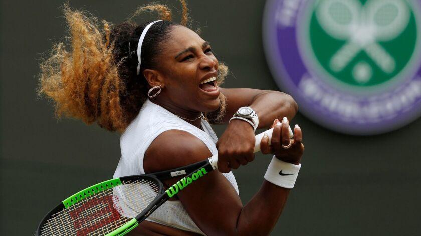 Serena Williams hits a return during a match at Wimbledon.