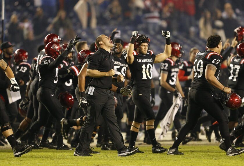 The Aztec sideline erupts in celebration after a review confirmed their winning touchdown in overtime during SDSU's football game against Boise State Saturday night at Qualcomm Stadium.