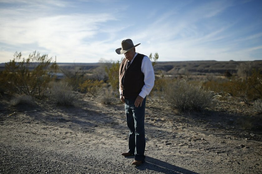 FILE - In this Jan. 27, 2016, file photo, rancher Cliven Bundy stands along the road near his ranch in Bunkerville, Nev. Bundy, the father of the jailed leader of the Oregon refuge occupation, and who was the center of a standoff with federal officials in Nevada in 2014, was arrested in Portland on