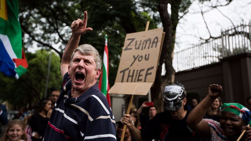 Protesters gather outside the Gupta family compound in Johannesburg, South Africa.