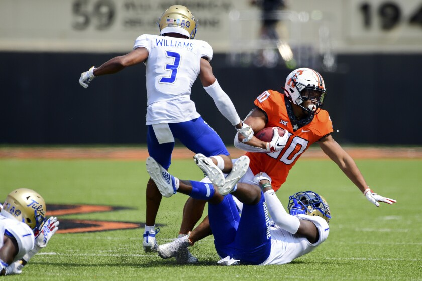 Oklahoma State running back Chuba Hubbard is tackled by Tulsa defenders in the second half of game in Stillwater, Okla.