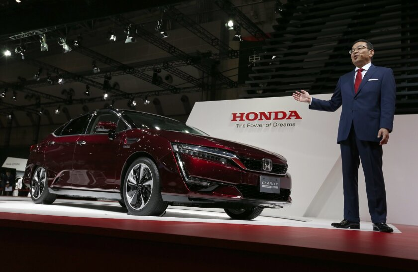 FILE - In this Wednesday, Oct. 28, 2015 file photo, Honda Motor Co. CEO Takahiro Hachigo speaks next to Honda FCX Clarity at Honda press conference during the media preview at the Tokyo Motor show in Tokyo. Honda reported a quarterly profit of 127.7 billion yen ($1 billion) Wednesday, Nov. 4, up 7